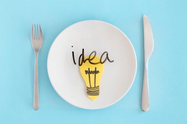 Texto de idéia com lâmpada amarela sobre o prato branco com garfo e faca de manteiga contra o fundo azul