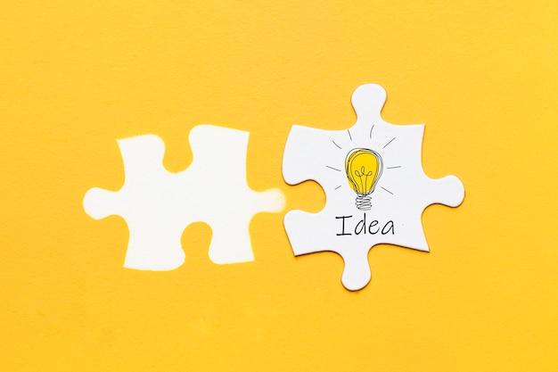 Texto de idéia e ícone na peça de quebra-cabeça com carimbo de peça de quebra-cabeça sobre fundo amarelo