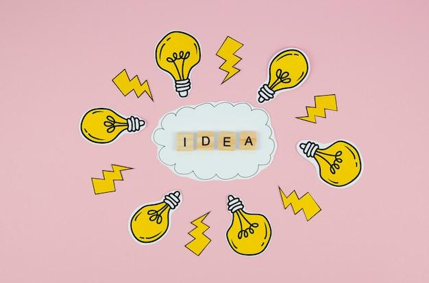 Texto de ideia na carta de rabiscos e lâmpadas em fundo rosa