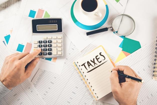 Texto de imposto de mão de homem no bloco de notas com calculadora no documento
