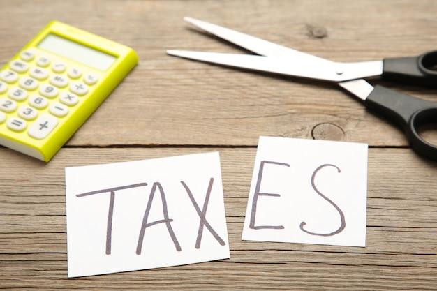 Texto de impostos e tesouras, conceito de redução de impostos em fundo cinza