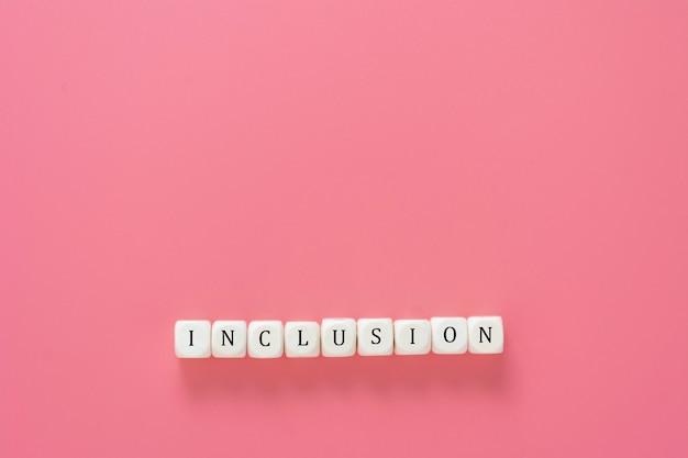 Texto de inclusão feito de cubos de madeira na mesa-de-rosa. conceito social inclusivo. copie o espaço.