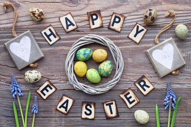 Texto de letras de páscoa feliz em madeira rústica com flores da primavera