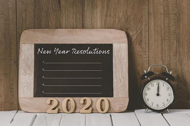 Texto de madeira 2020 e lista de resoluções de ano novo escritas na lousa com despertador