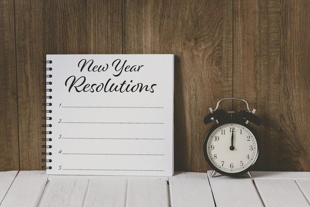 Texto de madeira 2020 e lista de resoluções de ano novo escritas no notebook com despertador