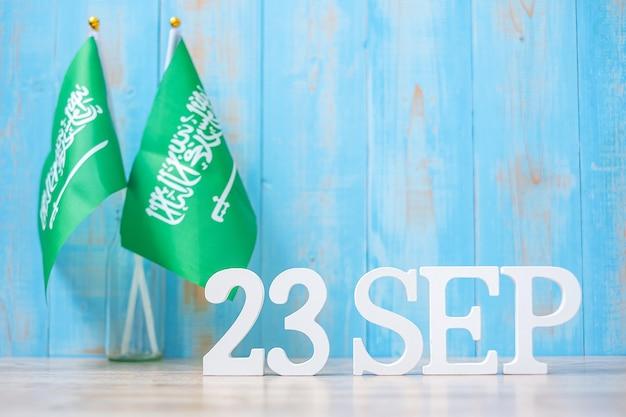 Texto de madeira de 23 de setembro com bandeiras da arábia saudita. dia nacional da arábia saudita de setembro e conceitos de celebração feliz