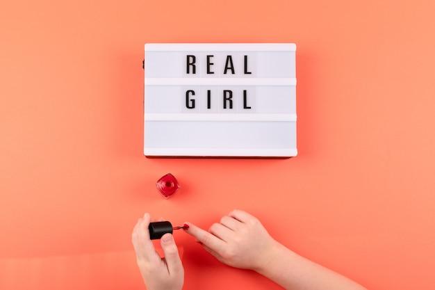 Texto de menina real nas mãos lightbox e menina pinta as unhas com esmalte vermelho sobre fundo coral