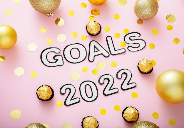 Texto de metas de 2022 com confetes dourados de decorações de natal sobre fundo de cor rosa. letras de metas 2022 no estilo de feliz ano novo.