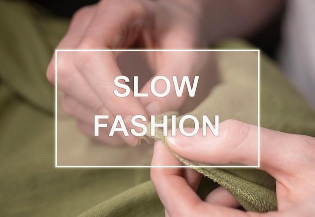 Texto de moda lenta sobre foto de mãos de alfaiate com agulha e linha com têxteis.
