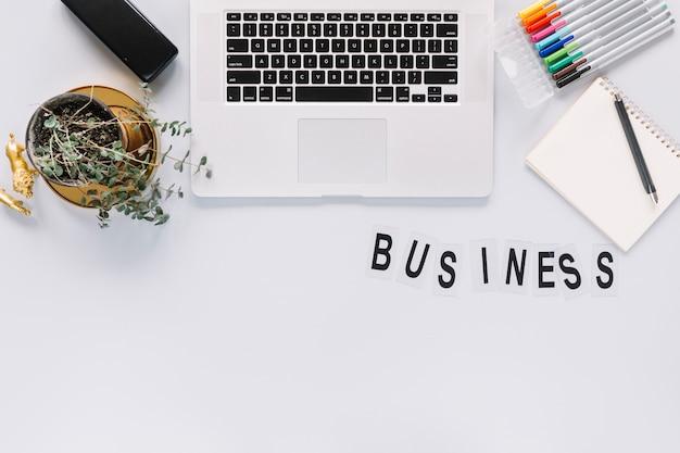 Texto de negócios com laptop e papelaria no fundo branco