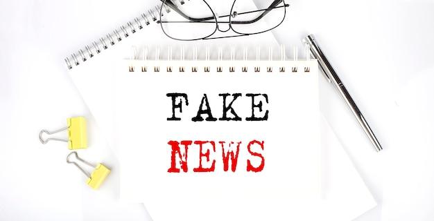 Texto de notícias falsas no caderno com caneta, clipes e óculos