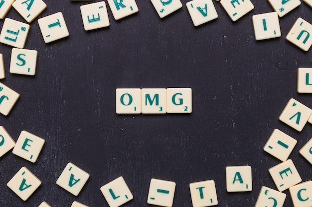 Texto de omg feito de cartas de jogo de scrabble