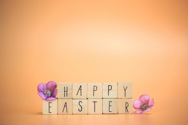 Texto de páscoa feliz em cubos de madeira com flores roxas da primavera
