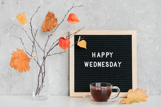 Texto de quarta-feira feliz no quadro de letra preto e buquê de ramos com folhas amarelas em prendedores de roupa em um vaso na mesa