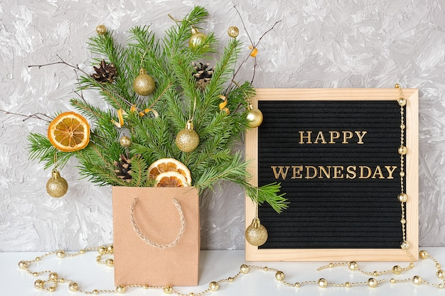 Texto de quarta-feira feliz no quadro de letra preto e buquê festivo de ramos de abeto com decoração de natal em pacote de artesanato
