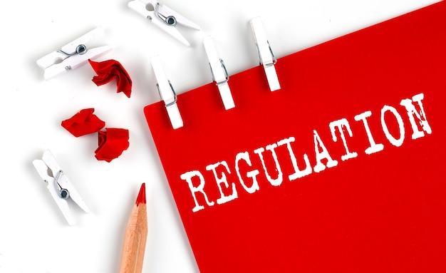 Texto de regulamento em papel vermelho com ferramentas de escritório em fundo branco