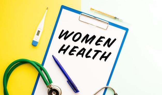 Texto de saúde feminina em um papel timbrado em uma pasta médica em um fundo bonito, estetoscópio e medicação.