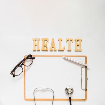 Texto de saúde perto da área de transferência com óculos; estetoscópio e caneta em fundo branco