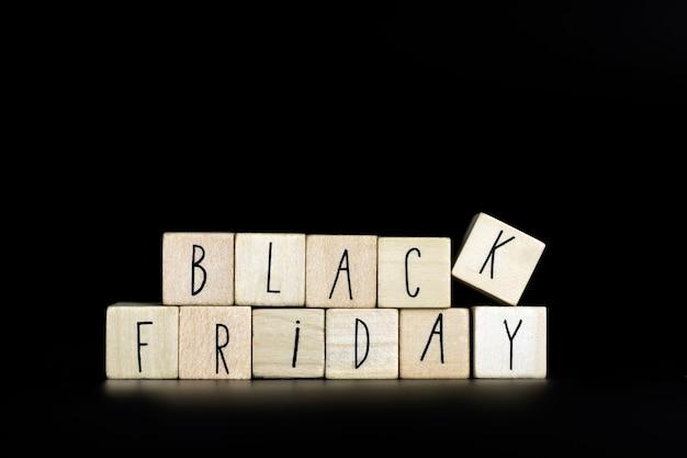 Texto de sexta-feira negra escrito com cubos de madeira em fundo preto horizontal simplicidade moderna backgro ...