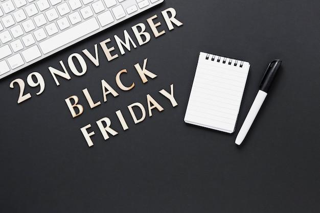 Texto de sexta-feira preta vista superior com bloco de notas de papel