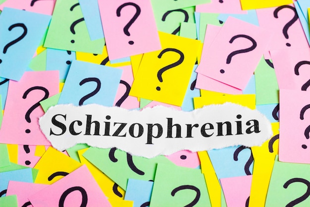 Texto de síndrome de esquizofrenia em notas auto-adesivas coloridas contra o de pontos de interrogação