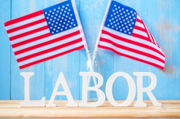 Texto de trabalho e a bandeira dos estados unidos da américa no fundo da mesa de madeira. feliz dia do trabalho e conceitos de celebração do feriado