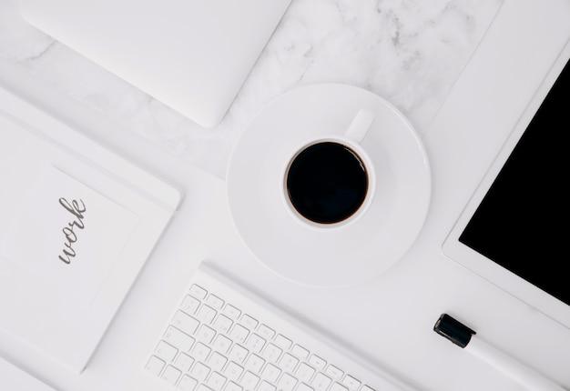 Texto de trabalho no diário; tablet digital; xícara de café; teclado e marcador preto na mesa branca