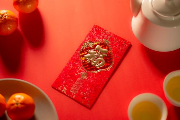 Texto de tradução no envelope vermelho na imagem: prosperidade e primavera. ano novo chinês e ano novo lunar celebrações envelope vermelho chá quente e laranja.