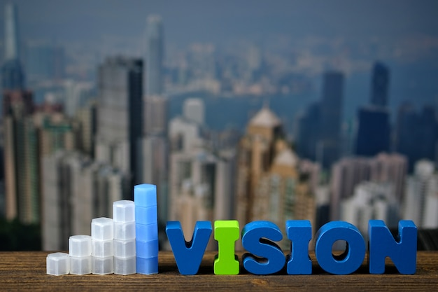 Texto de visão e gráfico na madeira superior com fundo da cidade da cidade