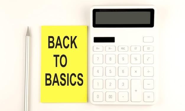 Texto de volta ao básico no adesivo amarelo, ao lado de uma caneta e calculadora
