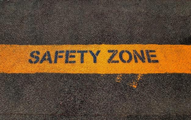 Texto de zona de segurança amarelo no chão de asfalto grunge escuro