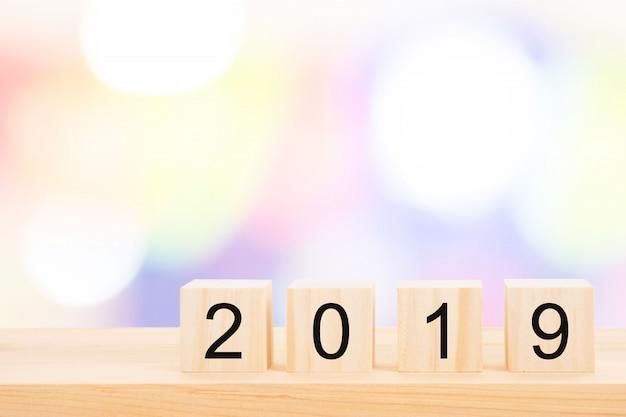 Texto do ano novo feliz 2019 em cubos de madeira na tabela de pinho de madeira e no bokeh claro do borrão.