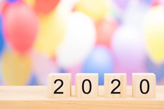 Texto do ano novo feliz 2020 em cubos de madeira na tabela de pinho de madeira e no bokeh claro do borrão.