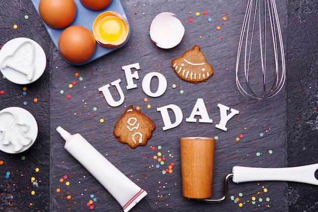 Texto do dia do ovni e biscoitos na forma de um disco voador e um alienígena. conceito de dia ovni