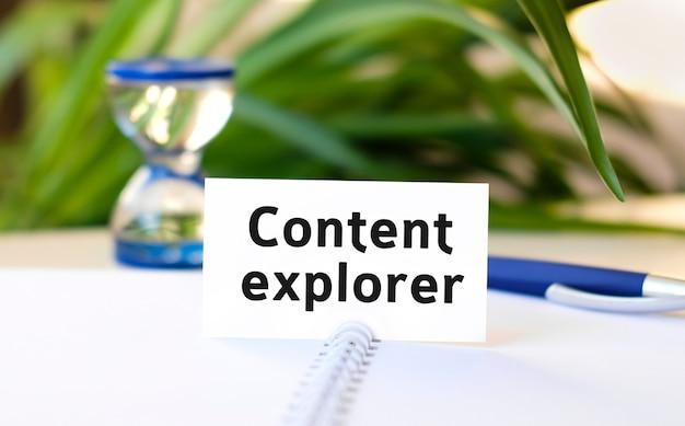 Texto do explorador de conteúdo em um caderno branco, ampulheta e caneta azul Foto Premium