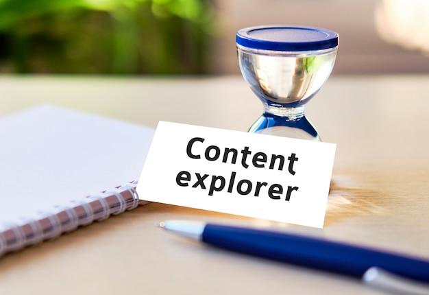 Texto do explorador de conteúdo em um caderno branco, relógio de ampulheta e caneta azul
