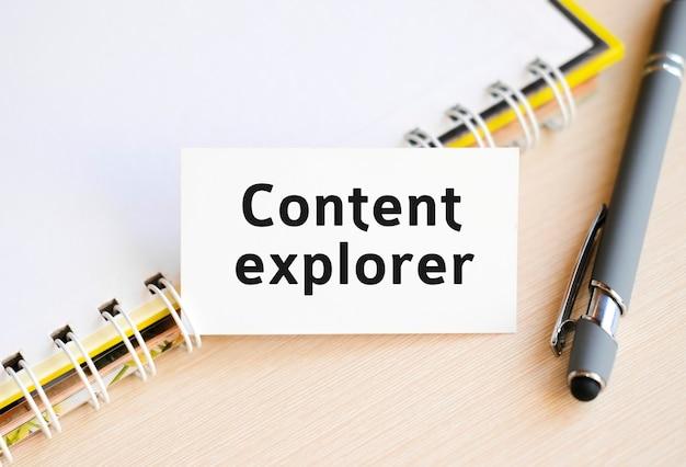 Texto do explorador de conteúdo em um caderno com uma mola e uma caneta cinza
