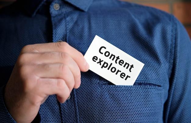Texto do explorador de conteúdo em uma placa branca na mão de um homem de camisa