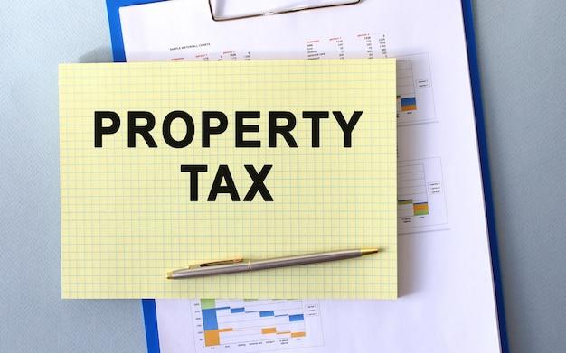 Texto do imposto sobre a propriedade escrito em bloco de notas a lápis. bloco de notas em uma pasta com diagramas.