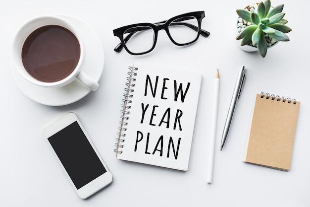 Texto do plano de ano novo no bloco de notas com acessórios de escritório