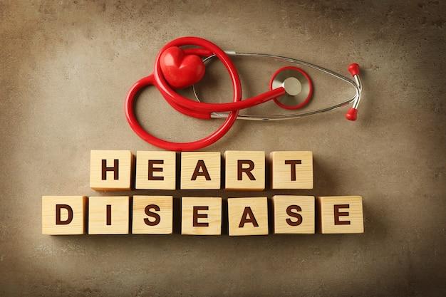 Texto doença cardíaca feito de cubos de madeira e estetoscópio na cor de fundo