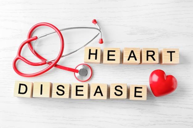 Texto doença cardíaca feito de cubos e estetoscópio sobre fundo de madeira