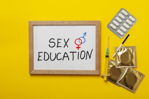 Texto educação sexual, teste de gravidez, seringa, pílulas e preservativos na superfície amarela