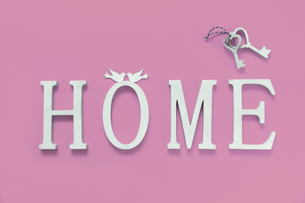 Texto em casa, de madeira, com uma decoração de forma de coração no fundo rosa. conceito de construção de casas, escolha de sua própria casa, hipoteca, compra, venda de área residencial, aluguel, seguro, investimento imobiliário.