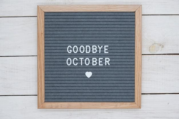 Texto em inglês adeus de outubro e um sinal de coração em uma placa de feltro cinza em uma moldura de madeira.