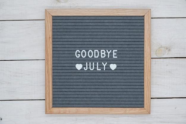 Texto em inglês adeus julho e um sinal de coração em uma placa de feltro cinza em uma moldura de madeira