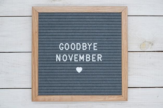 Texto em inglês adeus novembro e um sinal de coração em uma placa de feltro cinza em uma moldura de madeira