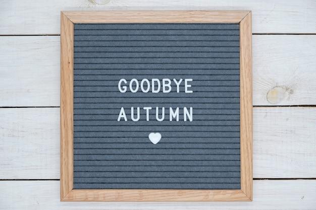 Texto em inglês adeus outono em uma carta board em letras brancas sobre um fundo cinza e um símbolo do coração.