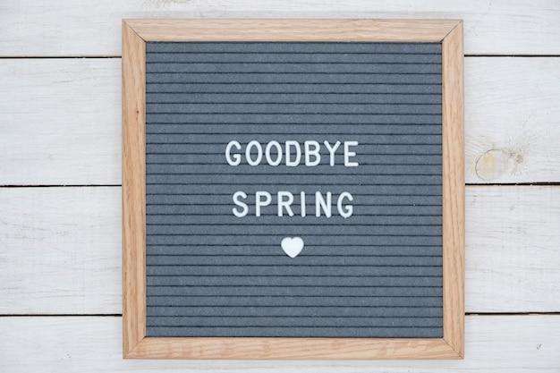Texto em inglês adeus primavera em uma carta board em letras brancas sobre um fundo cinza e um símbolo do coração.