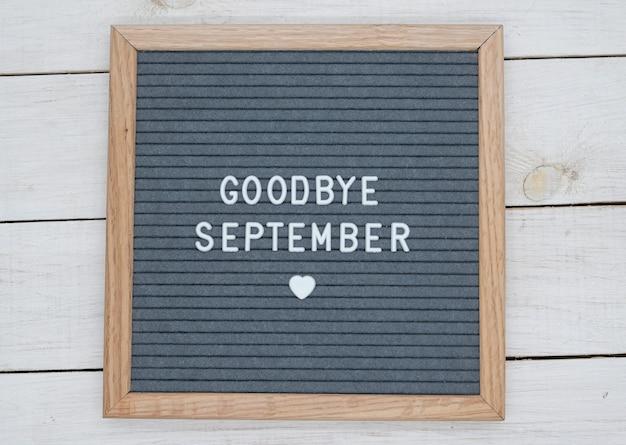 Texto em inglês adeus setembro e um sinal de coração em uma placa de feltro cinza em uma moldura de madeira.